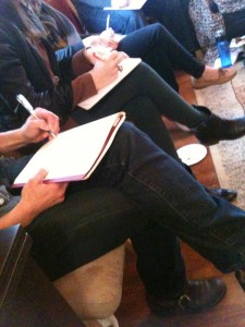 Photo of three pairs of crossed legs, on which notebooks are resting and pens are moving