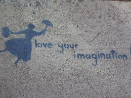 "graffiti of the words ""love your imagination"" next to a woman holding an umbrella, apparently floating..."