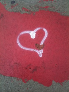 white spray-painted heart on red background, painted on Mass Ave sidewalk in Boston