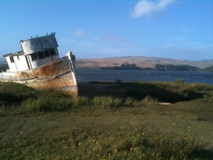 again the weathered boat, but from a wider angle: there's the grass and the mountains and the bay, behind