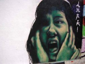 graffiti of a woman holding her cheeks and screaming