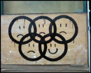 graffiti: interlocked Olympic rings, four with frowning faces and one with a smiling face