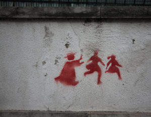 stencil graffiti, silhouette of priest chasing two children