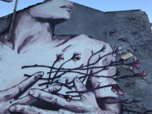 graffiti image of a woman holding her hands over her chest; branches are growing out of her