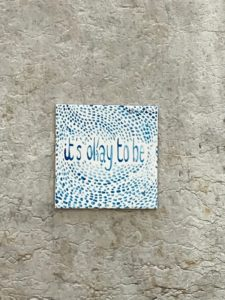 "photo of a tile pasted to a wall, painted with blue lines and the words ""it's okay to be"""
