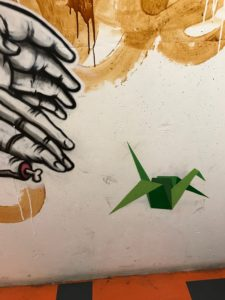 graffiti of hands reaching toward a green origami bird