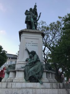 statue of a man standing on top of a pedestal; below, at the base, is a statue of a woman and child - the woman points, directing her child's attention to the man standing up top -- meanwhile, her ankle is still chained