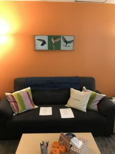 Comfy blue couch in front of a bright orange wall; on the wall hangs a painting of three hummingbirds