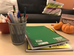 photo of notebooks and a cup full of pens on a table in front of an inviting couch