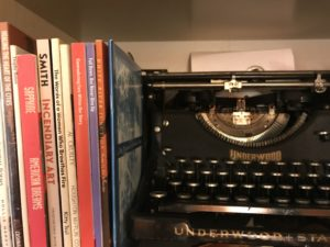 Photo of an old style typewriter next to a collection of poetry chapbooks