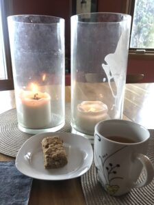 candles, tea, and peanut butter bar on a plate
