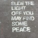 "Stencil graffiti reading, ""Slide the light off you may find some peace"""