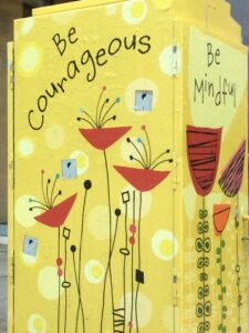 "Berkeley graffiti -- red flowers on a yellow background, beneath the words ""Be Courageous"""